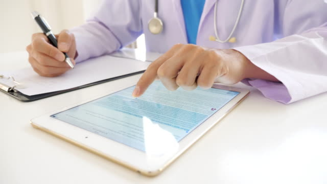doctor using digital tablet and writing on medical chart in hospital - clinica medica video stock e b–roll
