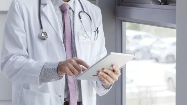 vídeos de stock e filmes b-roll de doctor using digital tablet by window in hospital - inclinado