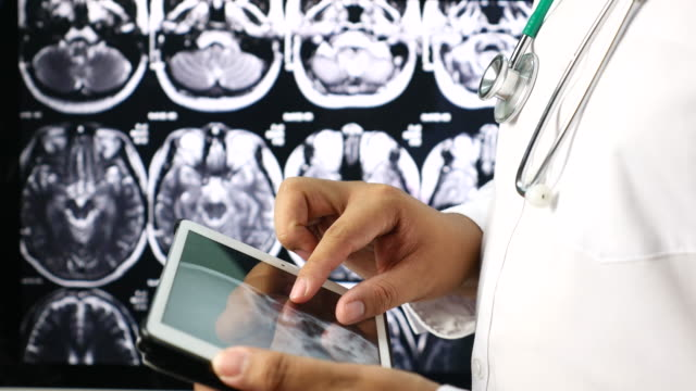 Doctor using digital tablet for Examining X-Ray Image with stethoscope, Healthcare And Medicine Concept