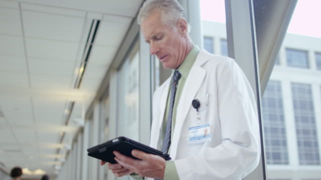 Doctor using digital tablet in hospital corridor