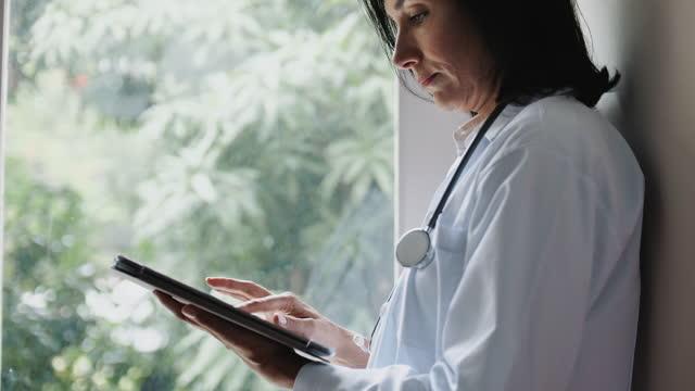 vidéos et rushes de docteur utilisant la tablette numérique - manteau et veste