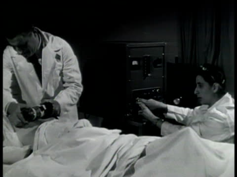 doctor using geiger counter on patient's back in hospital bed ms geiger counter on patient's back ms nurse operating count machine medical... - contatore geiger video stock e b–roll
