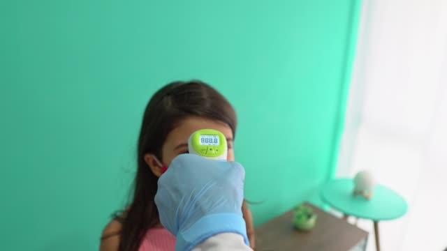 醫生使用紅外測溫儀檢查女孩的體溫。 - 熱度 溫度 個影片檔及 b 捲影像