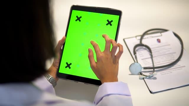 vídeos de stock e filmes b-roll de doctor using tablet green screen - seguro médico