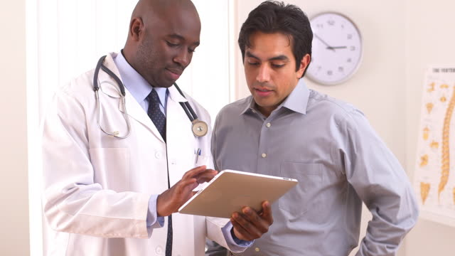 doctor using tablet pc with patient
