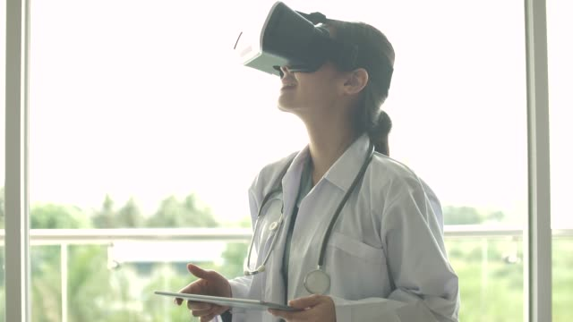 stockvideo's en b-roll-footage met doctor met behulp van virtual reality headset voor de zorgverlener - science and technology