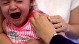Doctor vaccinates the baby sitting in the arms of the mother. Crying baby, medical manipulations, pediatrics concept. Immunization program.