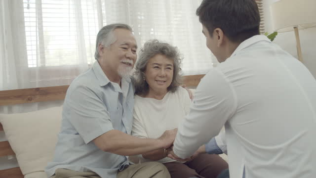 doctor visitor and exam to asian elder couple - examination gown stock videos & royalty-free footage