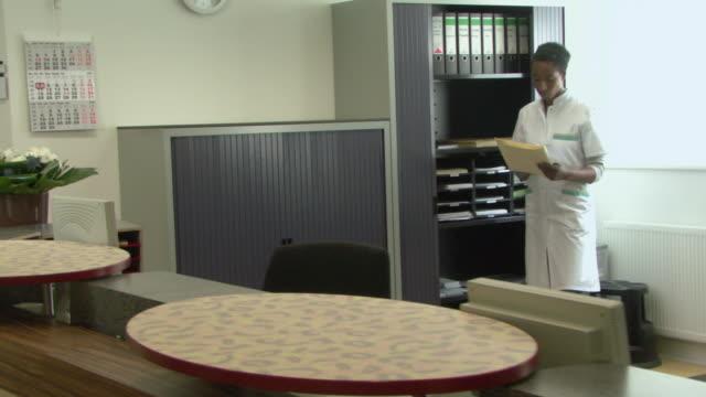 vídeos de stock e filmes b-roll de ws pan doctor walking over to computer in medical office - sentar se