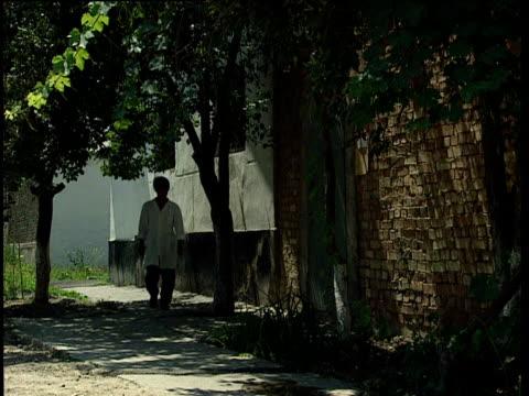 stockvideo's en b-roll-footage met doctor walks along path in grounds of drugs rehabilitation centre unlocks metal door and enters tajikistan - clean
