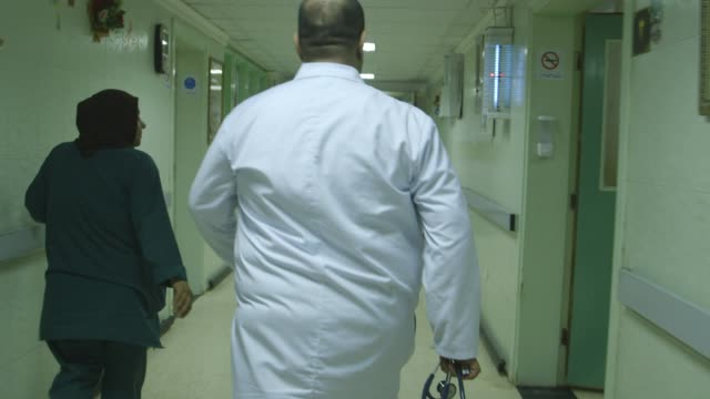 doctor walks through baghdad hospital, shot from behind - baghdad stock videos & royalty-free footage