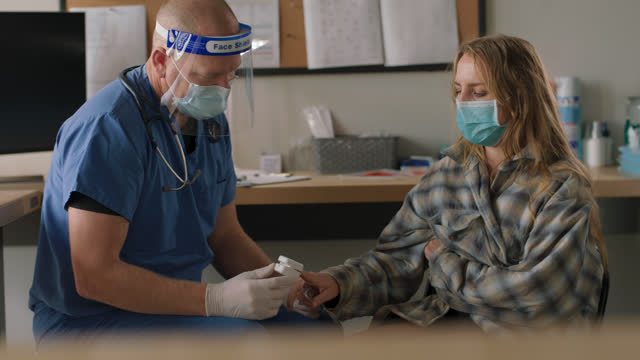 doctor wearing ppe places pulse oximeter on the finger of a female patient struggling with substance abuse - substance abuse stock videos & royalty-free footage