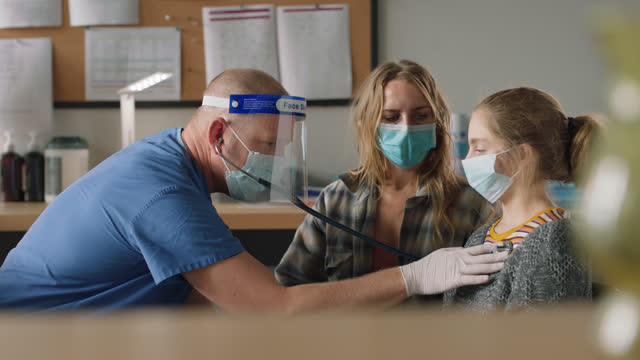 doctor wearing ppe uses stethoscope to listen to a young female patient's lungs - exam stock videos & royalty-free footage