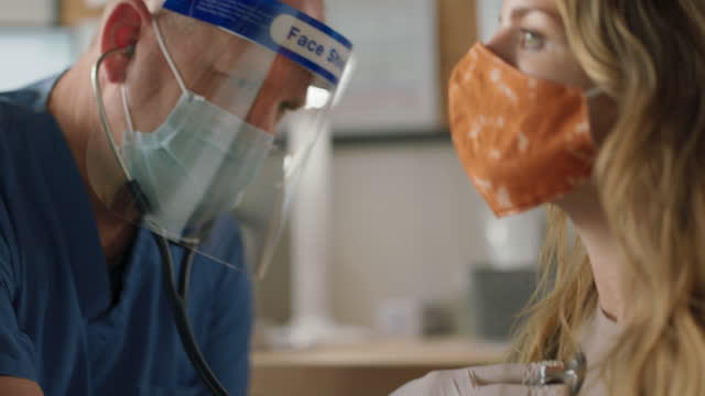 cu doctor wearing ppe uses stethoscope to listen to female patient's lungs - exam stock videos & royalty-free footage