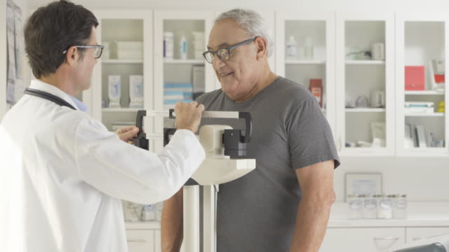 doctor weighing a senior man - waage gewichtsmessinstrument stock-videos und b-roll-filmmaterial