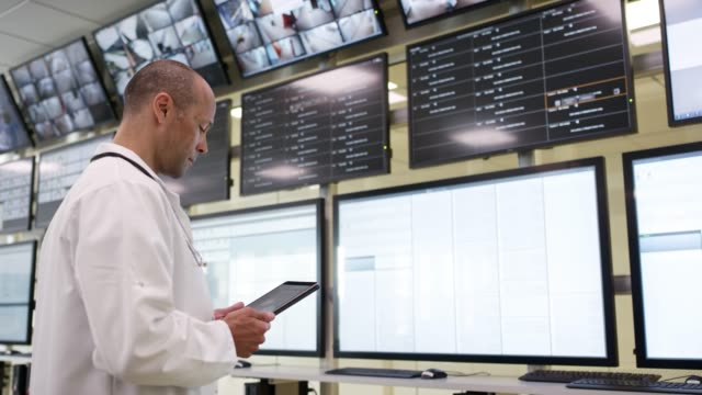 doctor with digital tablet looking at monitors - sala di controllo video stock e b–roll