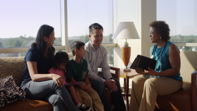 doctor with digital tablet talking to family in hospital lobby - waiting room stock videos & royalty-free footage