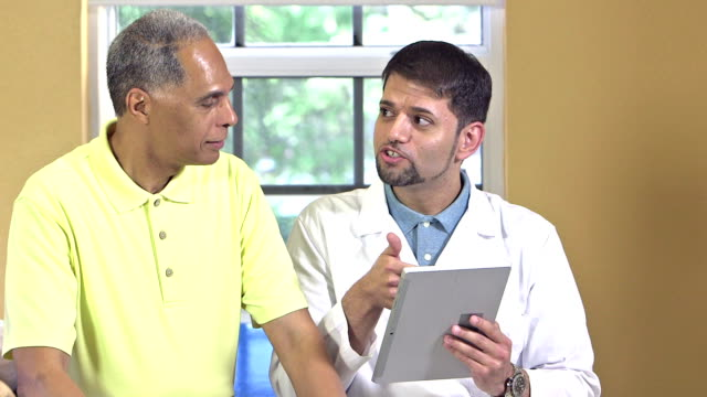 医師、デジタルタブレットを患者に話している - 説明する点の映像素材/bロール