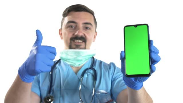 白い背景にクロマキーの緑の画面とスマートフォンを保持保護マスクと医師 - 空白の画面点の映像素材/bロール