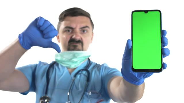 stockvideo's en b-roll-footage met arts met beschermend masker dat duimen onderaan teken toont en slimme telefoon met chroma zeer belangrijk groen scherm op witte achtergrond houdt - wit scherm
