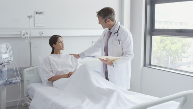 doctor with report discussing with patient in ward - examination gown stock videos and b-roll footage