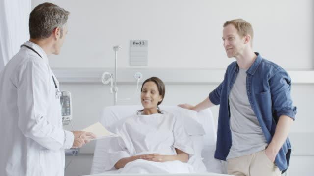 vídeos y material grabado en eventos de stock de médico con informes discutiendo con la pareja en la sala - clínica médica