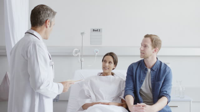 doctor with reports discussing with couple in ward - visit stock videos & royalty-free footage
