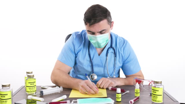 doctor with surgical gloves and protective mask holding coronavirus vaccine bottle and writing on blank yellow paper,dolly shot - prescription medicine stock videos & royalty-free footage