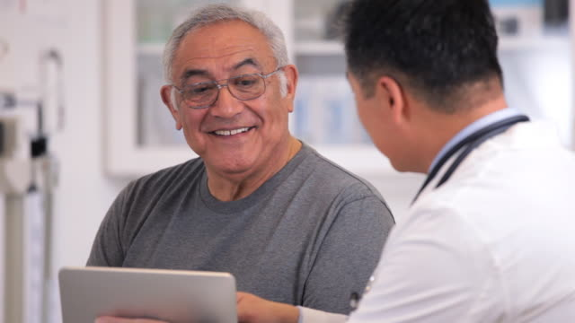 ms doctor with tablet computer talking to senior patient in exam room / richmond, virginia, usa - heilbehandlung stock-videos und b-roll-filmmaterial