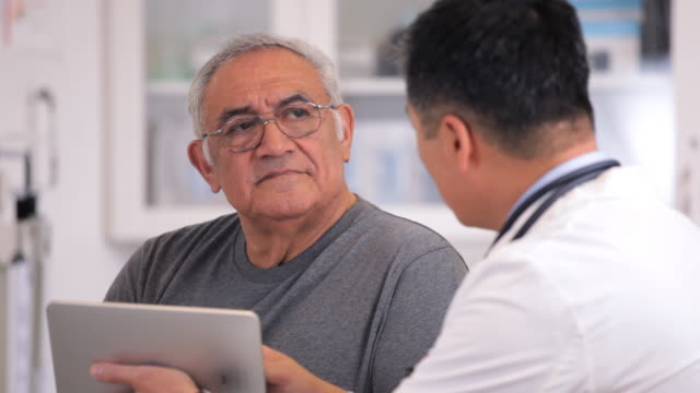 MS TU Doctor with Tablet Computer Talking to Senior Patient in Exam Room / Richmond, Virginia, USA