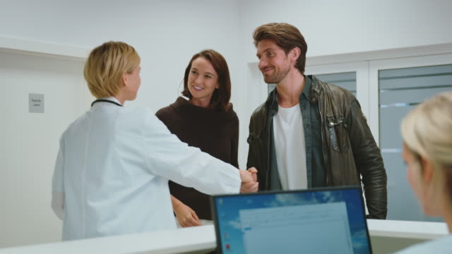 doctor with young couple at reception desk - leaving hospital stock videos & royalty-free footage