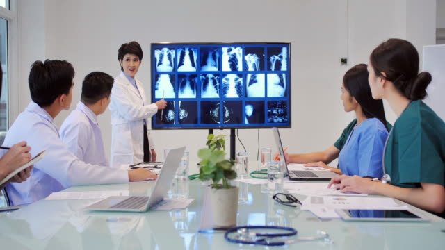 doctor women presenting x-ray during a meeting and young interns listening to doctor's lecture during medical conference.medical education, health care, medical education, people and medicine concept.education topics.women in stem - x ray equipment stock videos & royalty-free footage