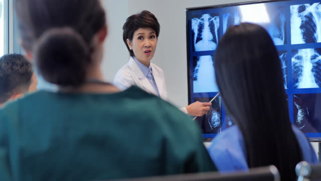 doctor women presenting x-ray during a meeting and young interns listening to doctor's lecture during medical conference.medical education, health care, medical education, people and medicine concept.education topics.women in stem - student leadership stock videos & royalty-free footage