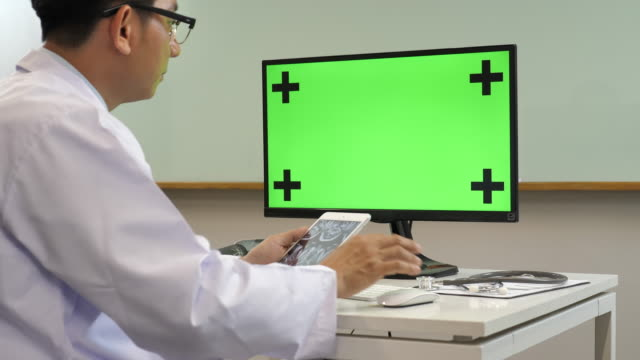 Doctor working computer with green screen at Hospitals
