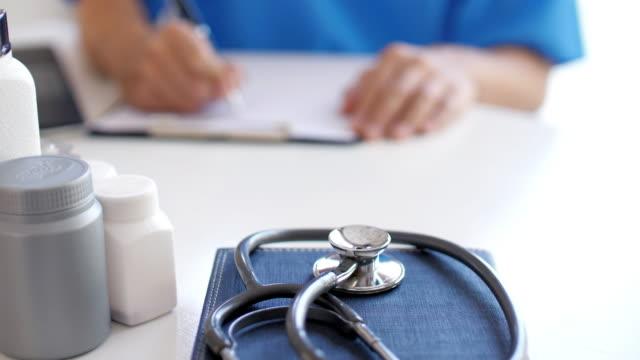 vídeos de stock e filmes b-roll de doctor working in hospital and filling patient information form on clipboard , slow motion - estetoscópio
