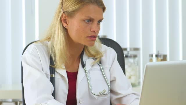 vídeos de stock e filmes b-roll de doctor working on her laptop - só uma mulher de idade mediana