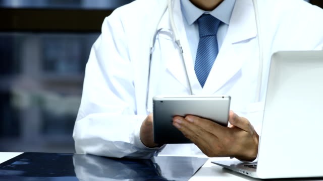 Doctor working with digital tablet in office