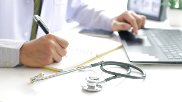 Doctor working with laptop and take a note and filling out medical document