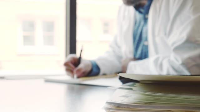 arzt arbeitet an seinem schreibtisch nach einem ganzen tag patientensehen - schreibtisch stock-videos und b-roll-filmmaterial
