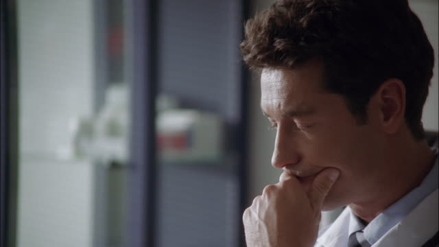 vidéos et rushes de a doctor worries as he sits in his office and does paperwork. - contemplation