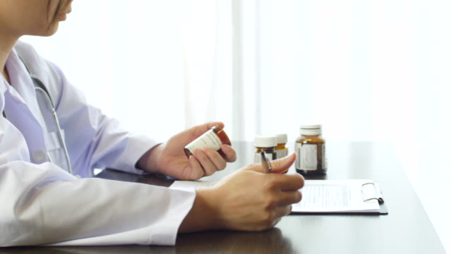 doctor writing a prescription medicine on clipboard with pill bottle - pill bottle stock videos & royalty-free footage