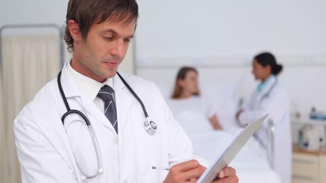 doctor writing on a clipboard - nur männer über 30 stock-videos und b-roll-filmmaterial