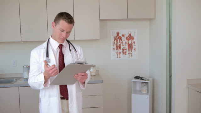 Doctor writing on clipboard and smiling at camera
