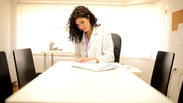 doctor writing  on desk in office - medical record stock videos & royalty-free footage