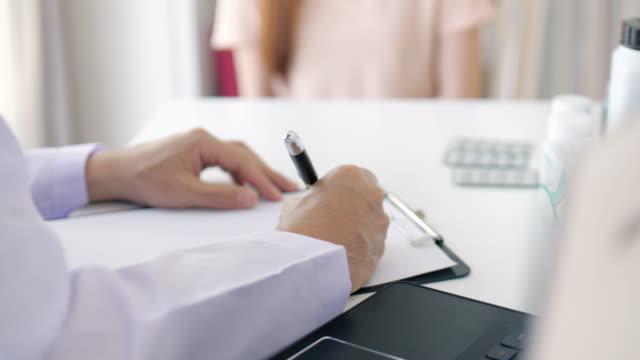 vídeos de stock e filmes b-roll de doctor writing prescription for patient at hospital - prescription medicine
