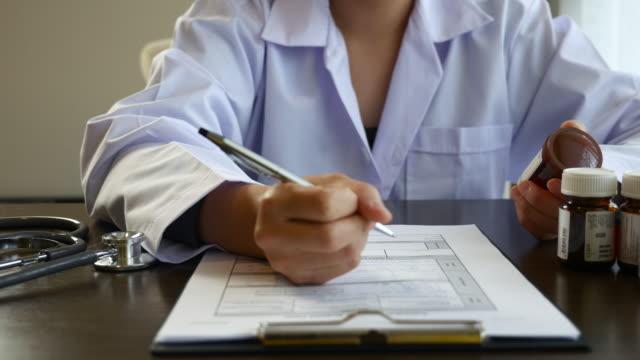 vídeos de stock, filmes e b-roll de médico escrevendo receita - quadro médico