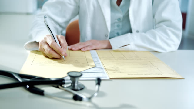 doctor writing the diagnose into the medical record - paperwork stock videos and b-roll footage