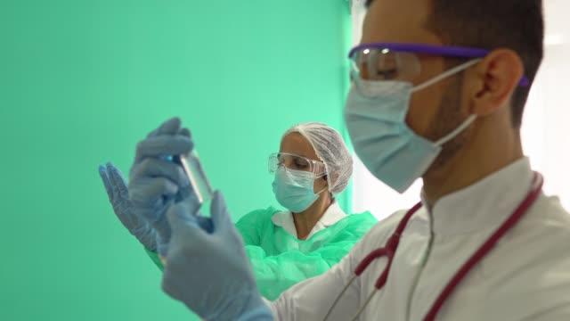 stockvideo's en b-roll-footage met artsen die geneesmiddelen in medisch overleg analyseren - medicijnflesje