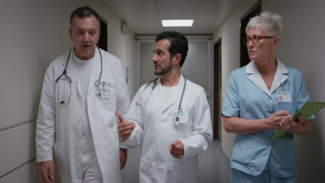 DS Doctors and a nurse talking while walking down the hospital hallway