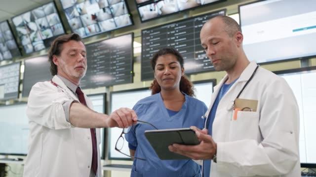 vídeos y material grabado en eventos de stock de los médicos y la enfermera discuten sobre la tableta digital - edificio médico